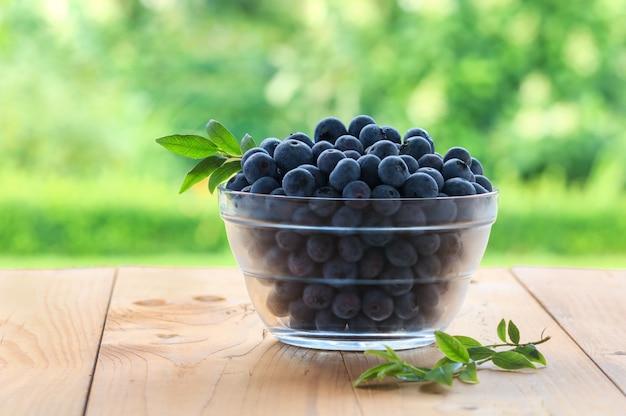 庭の木製テーブルの上にボウルに新鮮なブルーベリー