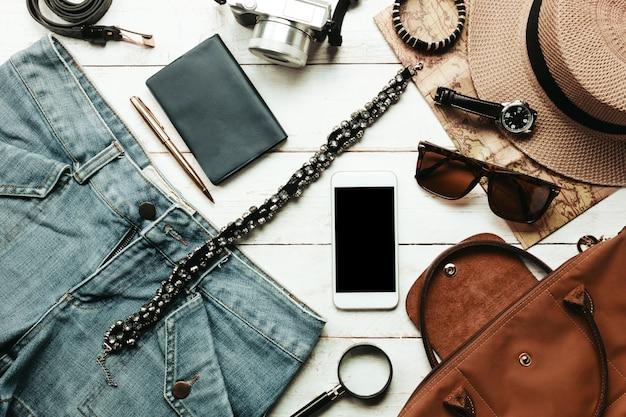 トップビューのアクセサリーは、女性の衣服のコンセプトと旅行する。白い木製テーブル上の携帯電話、時計、バッグ、帽子、マップ、カメラ、ネックレス、ズボン、サングラス。