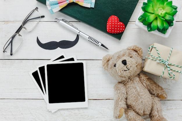 トップビュー幸せな父の日。木、ひげ、ヴィンテージの蝶のネクタイ、プレゼント、ペン、ノートブック、素朴な白い木製の背景にクマの人形とフリーテキストとアクセサリーのための塊の写真。