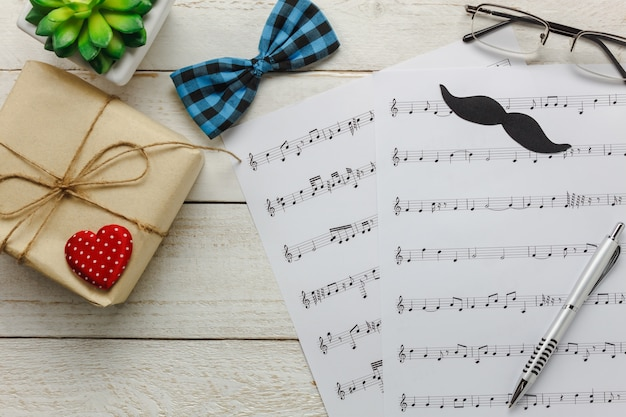 トップビューハッピー父の日、音楽のコンセプト。音符、赤い心、贈り物、口ひげ、ヴィンテージの蝶のネクタイ、ツリー、プレゼント付きの木製の背景。