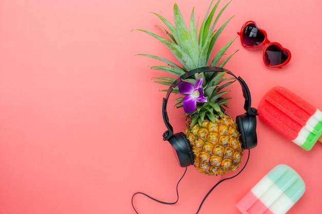 Плоское лежачее мороженое ананас прослушивание радио черными наушниками для обозначения сезонных.