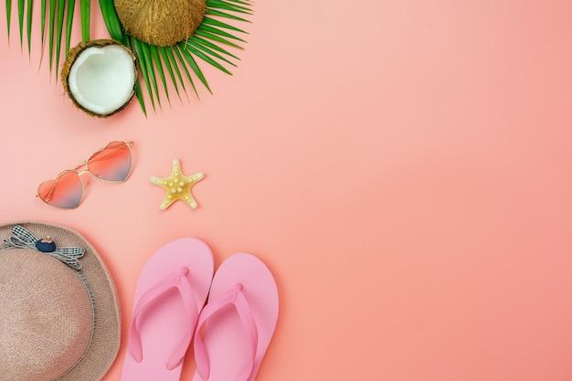 Необходимые предметы солнцезащитные очки и тапочки на современной деревенской розовой бумаге