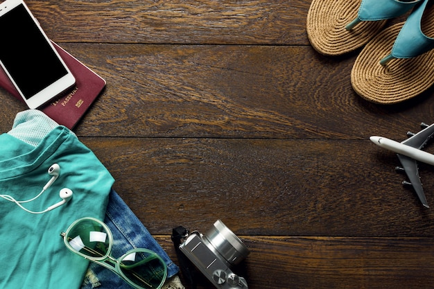 トップビューのアクセサリーは、携帯電話、カメラ、サングラス、布の女性、コピースペースの木製テーブル上のサンダルで旅行します。旅行のコンセプト。