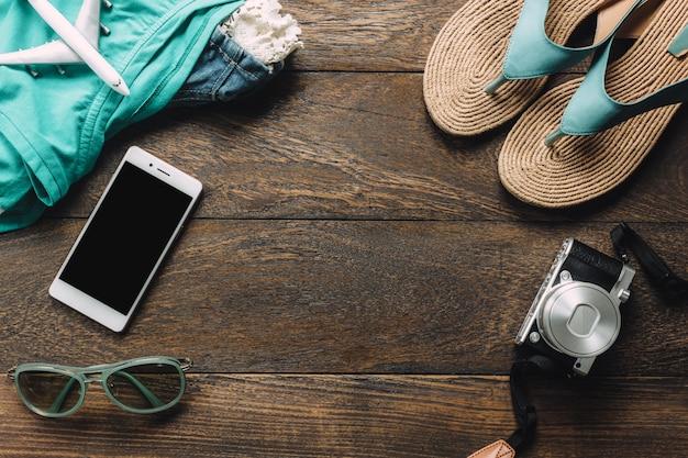 トップビューのアクセサリーは、携帯電話、カメラ、サングラス、布の女性、テーブルの上にサンダルをコピースペースと旅行する。旅行のコンセプト。