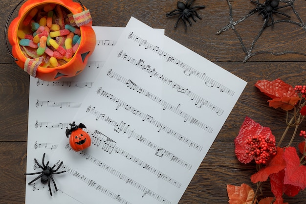 Вид сверху счастливого фестиваля хэллоуина и концепции фона для нот для нот. потрите или обработайте предметы с чашами и украшениями на современном коричневом столе. представьте себе идею разнотипного объекта на сезон с копией пространства.