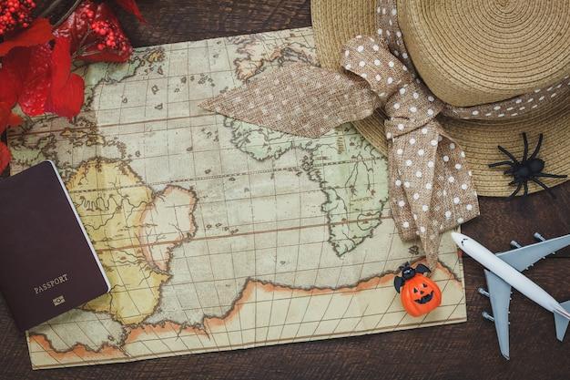 Верхний вид аксессуара счастливый хэллоуин с элементами для путешествий на фоне концепции. смешайте несколько объектов на современном деревенском коричневом деревянном столе на рабочем столе. оборудование для путешественника или подростка и для взрослых.