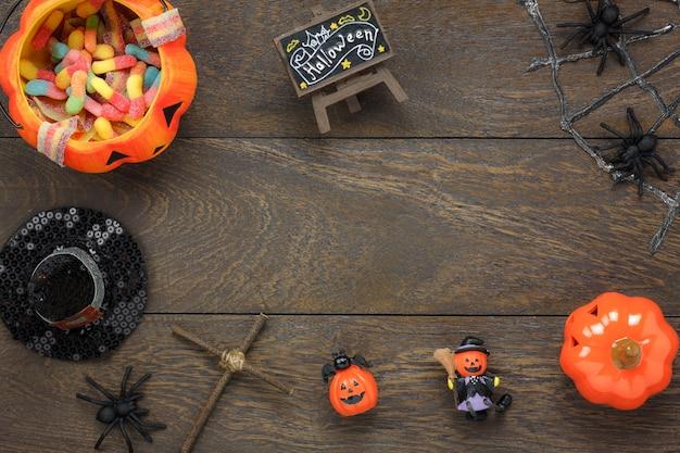 Плоский лак украшений аксессуаров счастливый праздник хэллоуина фон концепции. микс многообразный объект на современном деревенском коричневом деревянном столе на рабочем столе. необходимые предметы для украшения сезона.