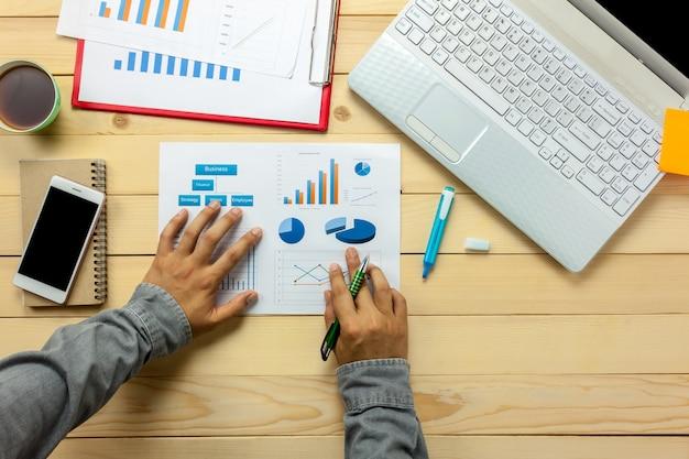 トップビュービジネスマンは、オフィスデスクでグラフやグラフを議論しています。