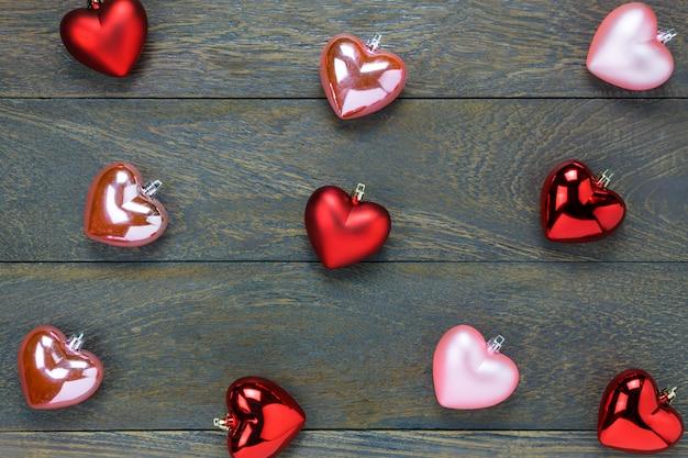 Вид сверху красный и розовый узор сердца на деревянном фоне.