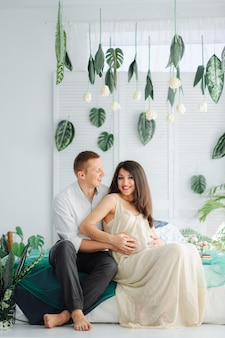 一緒にソファーでリラックスした妊娠中の女性とカップルします。