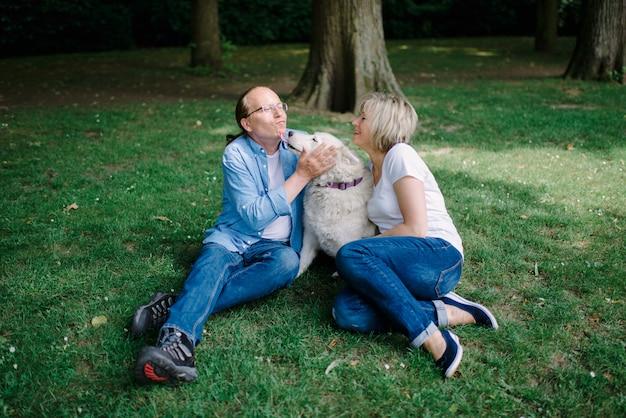 白い犬と草の上に座っている大人のカップル