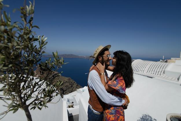 サントリーニ島の海と建築の背景にキス美しい若いカップル