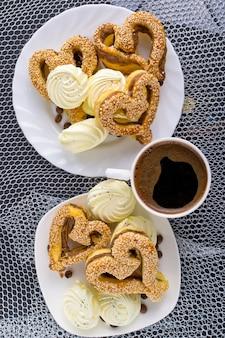 Печенье в форме сердца с кунжутом, зефиром и чашкой кофе на серебре