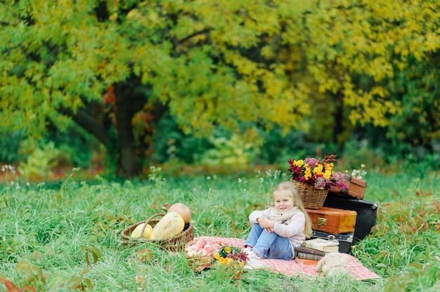 Маленькая девочка сидит на одеяле на траве