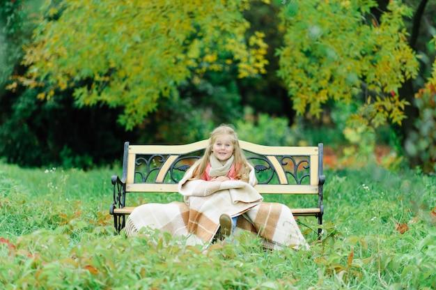 Маленькая девочка сидит на скамейке в природе