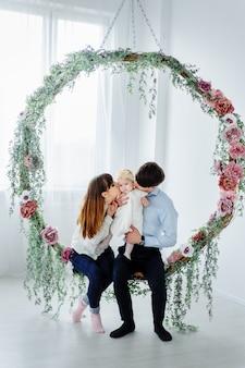 小さな赤ちゃんと一緒に座っている幸せな家族。家で娘と過ごす家族。