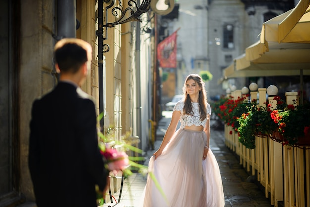 Мода длинноногая девушка в красивой обуви на высоких каблуках, сидя на набережной на закате лета
