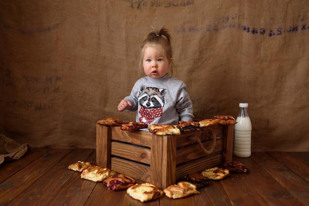 Маленькая девочка на кухне ест сладкую выпечку.