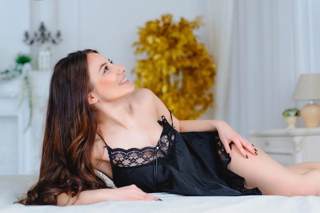 ベッドに横になっているランジェリーで魅力的なセクシーな女性の肖像画