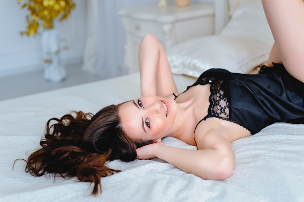 白いランジェリーのセクシーな若い女性はベッドにあり、枕を抱擁します。魅惑的な曲線。