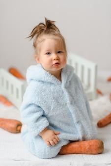 Маленькая девочка в костюме кролика ест морковь.