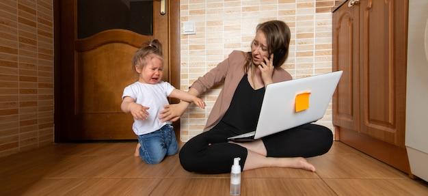若い美しい母親がリモートで作業しようとしています。彼女の小さな娘は彼女を悩ませています。
