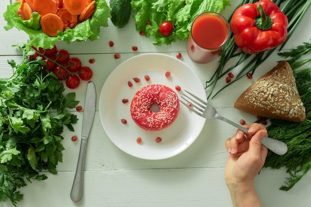 Вкусный пончик лежит на тарелке и ест его. проблемы правильного питания и концепция выбора между полезной и нездоровой пищей