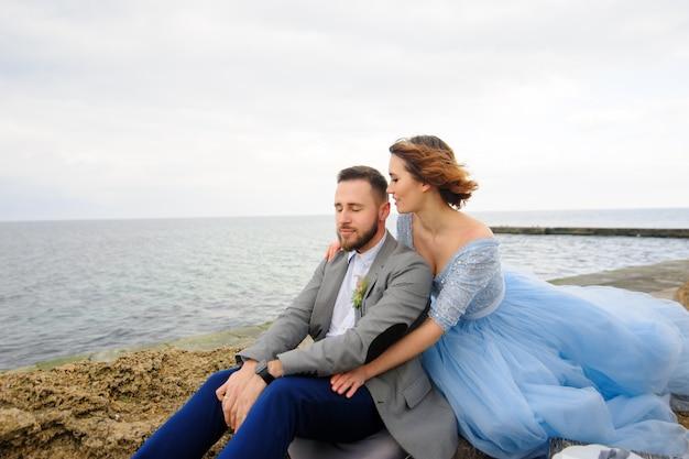 海岸でのカップルの結婚式のフォトセッション。花嫁の青いウェディングドレス。