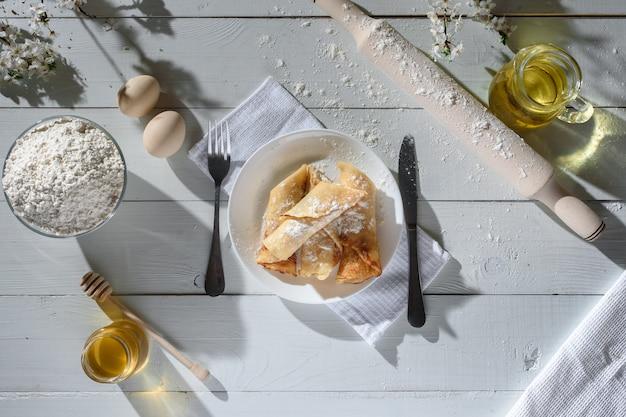 白い木製の背景にカッテージチーズのパンケーキ。蜂蜜、ヒマワリの種、小麦粉、卵で撮影します。伝統的な朝食。