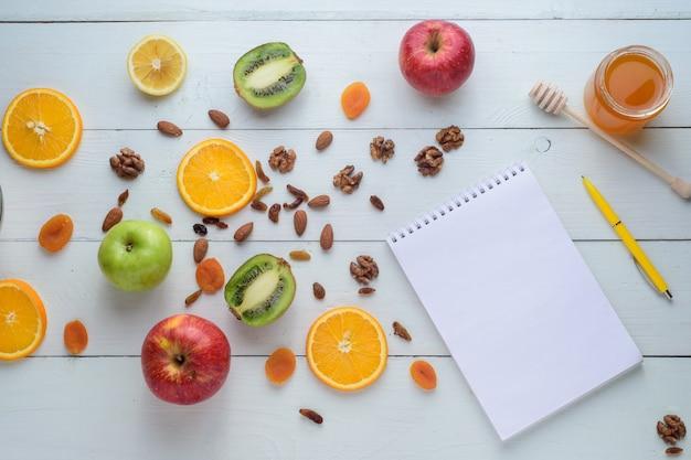 リンゴ、キウイ、ドライフルーツ、オレンジ、リンゴに囲まれたペンのノート。健康的な食事と買い物リストの概念。