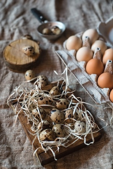Яйца перепелиные и куриные в деревянной коробке на фоне мешковины.