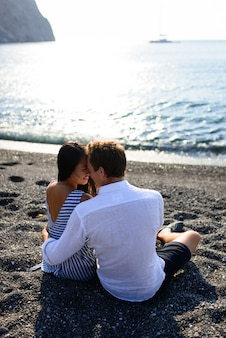Молодая красивая пара, поцелуи на фоне моря.