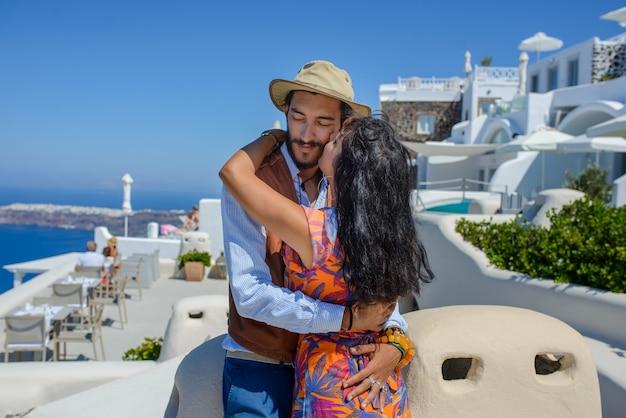 男と女がサントリーニ島のスカロスロックを背景に抱いています。イメロヴィグリの村。彼は民族のジプシーです。彼女はイスラエル人です。
