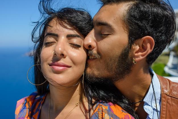 サントリーニ島のスカロスロックを背景に男性と女性がキスします。イメロヴィグリの村。彼は民族のジプシーです。彼女はイスラエル人です。