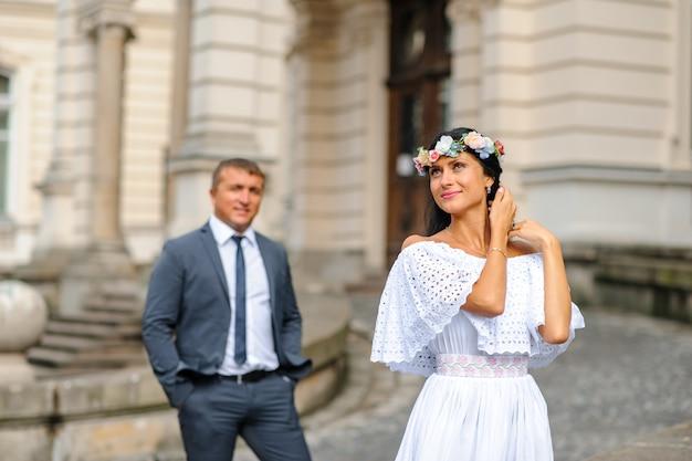 古い建物の背景での結婚式のフォトセッション。新郎は彼の花嫁のポーズを見る。素朴または自由奔放に生きる結婚式の写真。