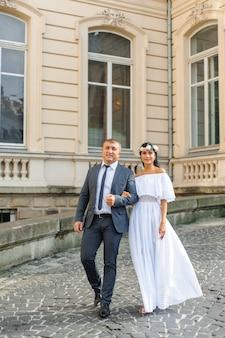 古い建物の背景での結婚式のフォトセッション。新郎新婦が一緒に歩いています。女性が男性の腕を握っています。素朴または自由奔放に生きるスタイルの結婚式の写真