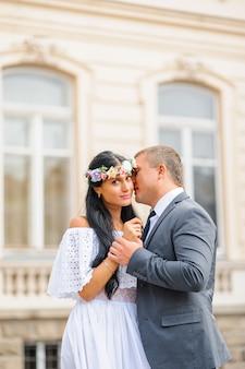 古い建物の背景での結婚式のフォトセッション。新郎新婦はお互いの手を握っています。