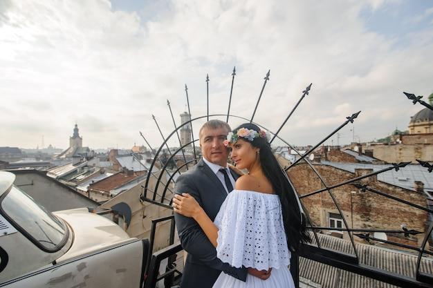 古い建物の屋上での結婚式の写真撮影。新郎新婦が抱いています。素朴または自由奔放に生きるスタイルの結婚式の写真