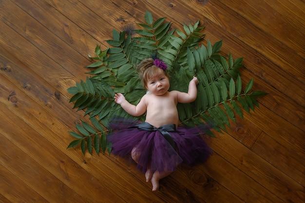 Портрет милая маленькая девочка (шесть месяцев) с венком из цветов на голове в помещении