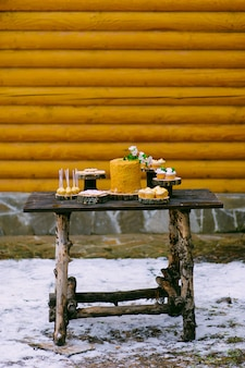 ウェディングキャンディバーの木製のテーブルの上のケーキ
