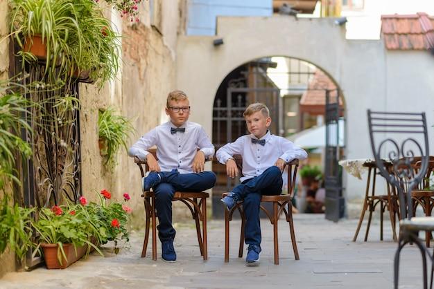 Две милые мальчики разговаривают сидя на деревянных стульях. мальчики подражают родителям бизнесменам. мальчики сидят на стульях со скрещенными ногами.