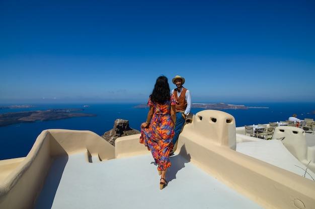 男と女がサントリーニ島のスカロスロックを背景にポーズします。イメロヴィグリの村。彼は民族のジプシーです。彼女はイスラエル人です。