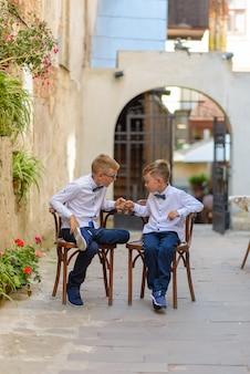 Две милые мальчики разговаривают сидя на деревянных стульях. мальчики подражают родителям бизнесменам. мальчики сидят на стульях со скрещенными ногами и бьют кулаками.