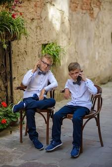 Две милые мальчики разговаривают на своем смартфоне. мальчики подражают родителям бизнесменам. ребята сидят на деревянных стульях на улице старого города.