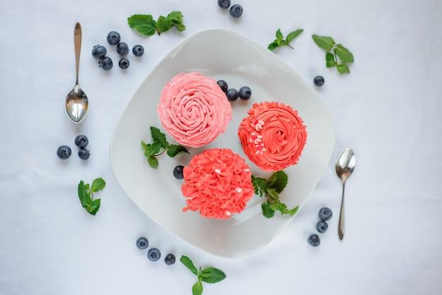 Вкусные разноцветные кексы на белом фоне на белом фоне.