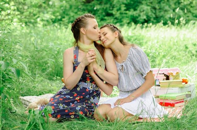 Мать и дочь обнимаются и скручены руки. мать целует дочь в лоб.