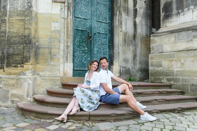 Двое влюбленных спиной друг к другу сидят на ступеньках старой церкви. влюбленные смотрят друг другу в глаза. пара счастлива.