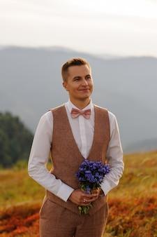 野の花の花束を持つ新郎が彼の花嫁を見ます。山での結婚式の写真。