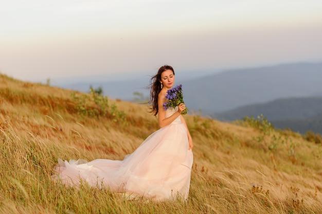 Портрет прекрасной невесты с букетом полевых цветов «васильки» на фоне пейзажей осенних гор. ветер дует на ее волосы. свадебная церемония на вершине горы.