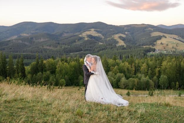 山での結婚式の写真。新婚夫婦はベールの下で抱いています。
